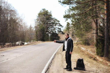 A young man is hitchhiking around the country. The man is trying