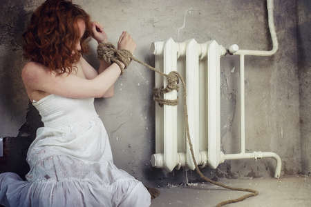 Young girl tied up on the floor. The abducted girl. The victim o