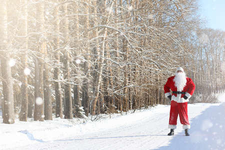 Santa Claus comes with gifts from the outdoor. Santa in a red suit