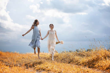 Two girls in dresses in autumn field