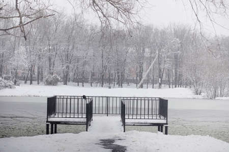 Snow-covered winter park and benches. Park and pier for feeding ducks and pigeons. The snow covered the autumn park. Banque d'images