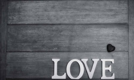 the word love made up of white wooden letters on a wooden background