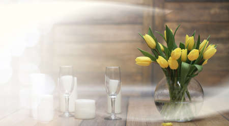 bouquet of yellow tulips in a vase on floor Stock Photo