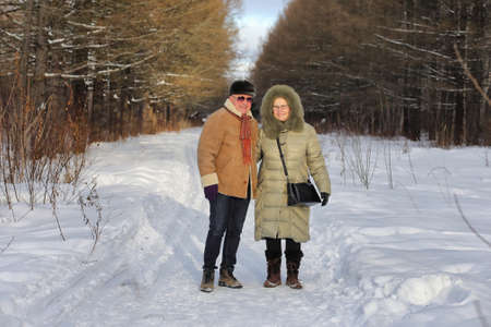 Old couple walk through the forest during winter Standard-Bild