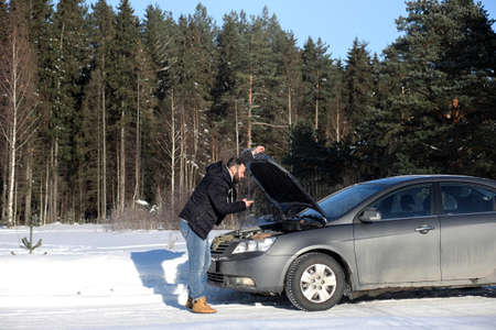 Man stands outdoor near broken car
