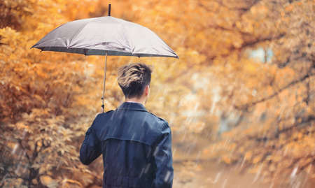Autumn park in rainy weather and a young man with an umbrella