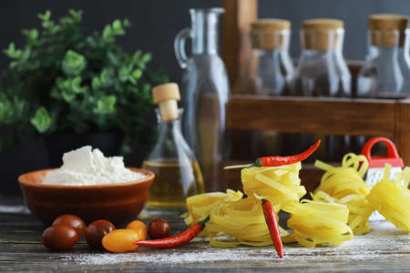 Pasta uncooked on the table. Noodles in the form of nests. Flour and seasonings. Stock fotó