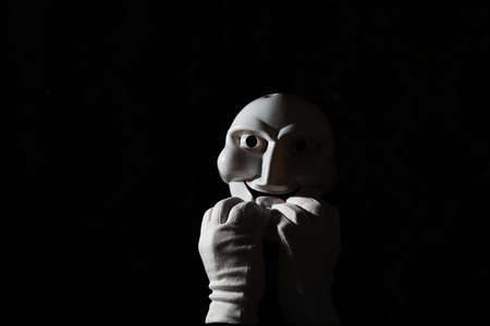 Máscara de miedo blanca sobre un fondo negro con manos blancas.