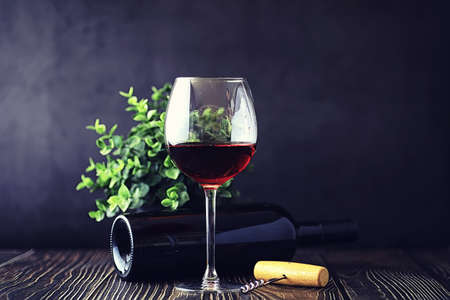 A glass of red dry wine on a table. Dark bottle and glass of wine. Reklamní fotografie