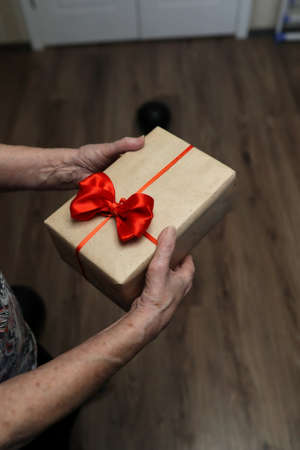 gift box with red bow in grandmother hands macro