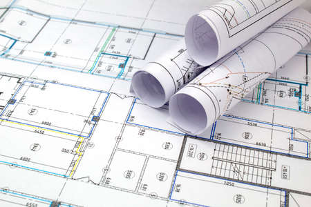 The drawings of the building under construction are rolled up and lie on a fragment of the deployed drawing. Standard-Bild