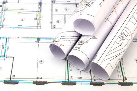 The drawings of the building under construction are rolled up and lie on a fragment of the deployed drawing.