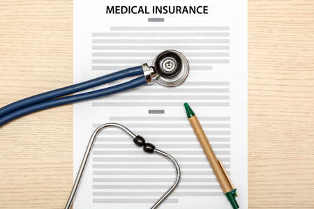 insurance themes: Stethoscope and pen laying on the blank of medical insurance on wood background. Stock Photo