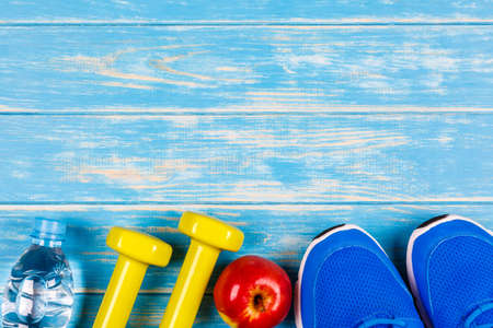 Bottle of water, dumbbells, sport shoes and apple on blue wood background.