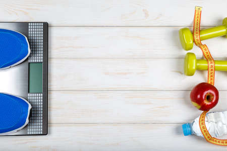 weigher: Bottle of water, dumbbells, sport shoes, measure tape, weigher and apple on white wood background. Concept plan.