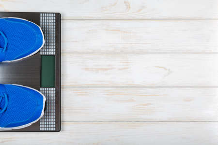 weigher: Sports shoes standing on the scales on white wood background. Concept plan. Stock Photo