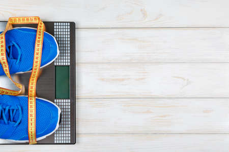 weigher: Sports shoes standing on the scales with measure tape on white wood background. Concept plan.