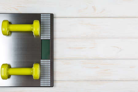 weigher: Dumbbells lying on the scales on white wood background. Concept plan. Stock Photo
