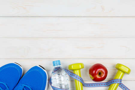 water concept: Bottle of water, dumbbells, sport shoes, measure tape and apple on white wood background. Concept plan.