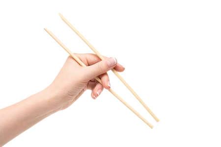 vietnamese ethnicity: Female hand holds chopsticks on a white background.
