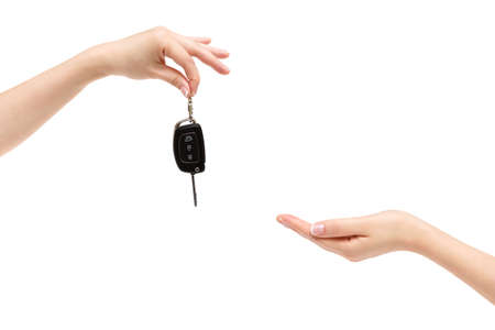 Female hand delivers car keys to other hand on a white background.