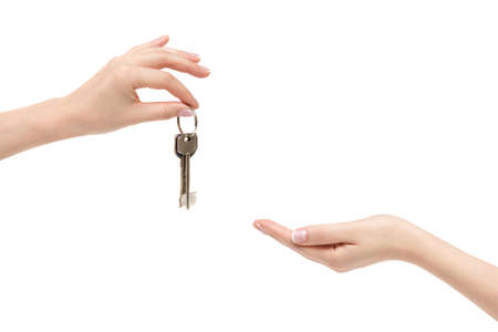 Isolated female hand delivers keys to other hand on white background.