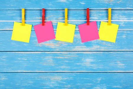 View of five yellow and red clothespins hanging on a rope with five cards on a blue background Stock Photo