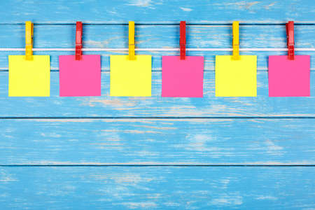 View of six yellow and red clothespins hanging on a rope with cards on a blue background