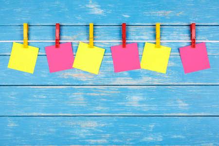 Gezicht op zes gele en rode doekjes die op een touw hangen met kaarten op een blauwe achtergrond