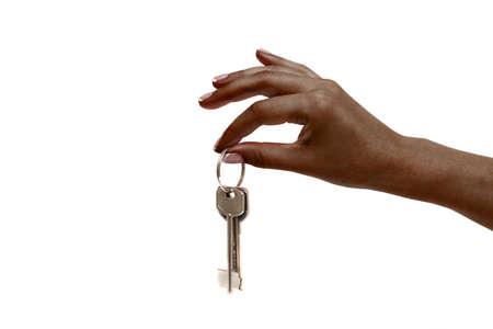 cerrando negocio: Mano femenina africana aislado sostiene las llaves en el fondo blanco. Foto de archivo