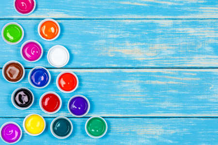 View of jars of colored paint on the blue wooden background