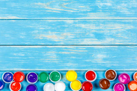 View of open cans of colored paint on the blue wooden background Stock Photo