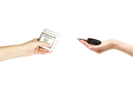 keyless: Isolated female hands hold car keys and stack of dollars on white background. Stock Photo