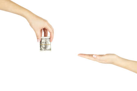 Women's hand is giving stack of money another hand on white isolated background. Foto de archivo