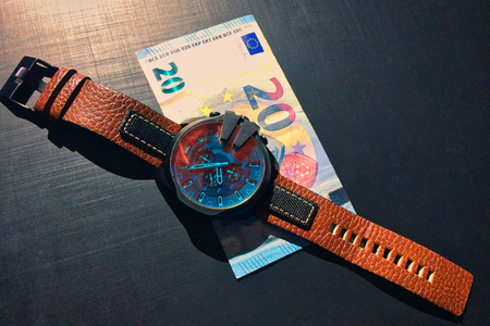 wrist watch with leather strap near the banknote on a dark background, watch on top of money, time is money, wristwatch, European currency, twenty euros 免版税图像