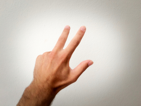 white man's palm, outstretched palm, hand on a white background, part of the body, part of the hand, white skin, three fingers, show the number, in the amount of three, hand gesture, the reverse side Banque d'images