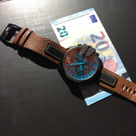 wrist watch with leather strap near the banknote on a dark background