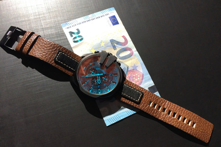 wrist watch with leather strap near the banknote on a dark background, watch on top of money, time is money, wristwatch, European currency, twenty euros Stock Photo