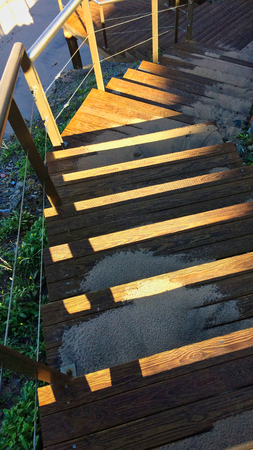 steep wooden staircase leading down, sand scattered on the steps, the suns rays play on the wood 写真素材