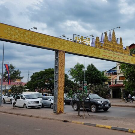Cambodia, Siem Reap 12/08/2018 Motor traffic on a city street in southeastern Asia, cloudy weather, yellow arch with inscriptions in Khmer language