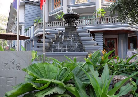 Siem Reap, Cambodia, December 12, 2018 dense tropical vegetation on a city street. Gardening of city streets. A small fountain near the hotel.