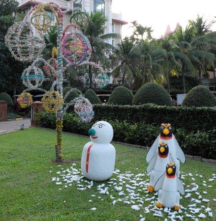 snowman and three penguins on a green lawn, garden sculpture, palm trees and decorative trees Stock Photo