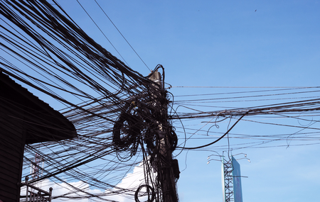 A column of power lines with a huge number of tangled wires. Power line. Chaos and the collapse of the urban electricity network. Banco de Imagens