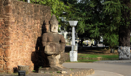 Ancient stone sculpture in a city park. A stone wall and a statue of a man. Asian artwork.