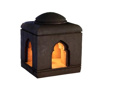 Unusual ceramic lantern. Dim light in the lantern. Isolated. White background.