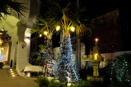 A small Buddhist sanctuary. Palm tree trunk, decorated with decorative lights. Night scene.