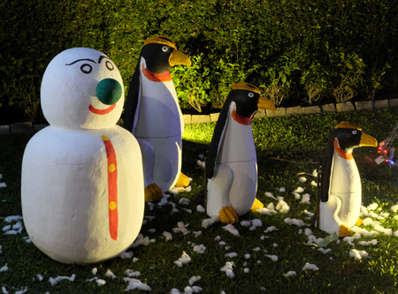 A snowman and three evil penguins are standing on a green lawn. Snowman with a green nose. Christmas celebration in countries with warm climates.