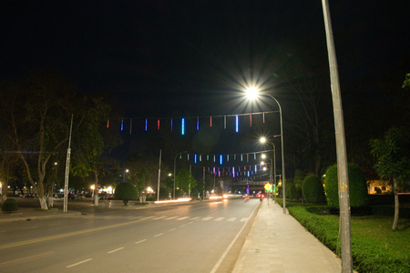 Wide and straight street of the city at night lit by lanterns. Road marking. Decorative lights above the road.