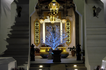 Richly decorated hall of the building. Unusual new year tree. Celebration of Christmas in the Buddhist country. Фото со стока