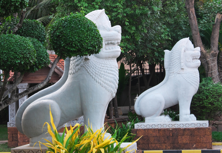 Two white stone sculptures of lions near beautifully trimmed ornamental trees.